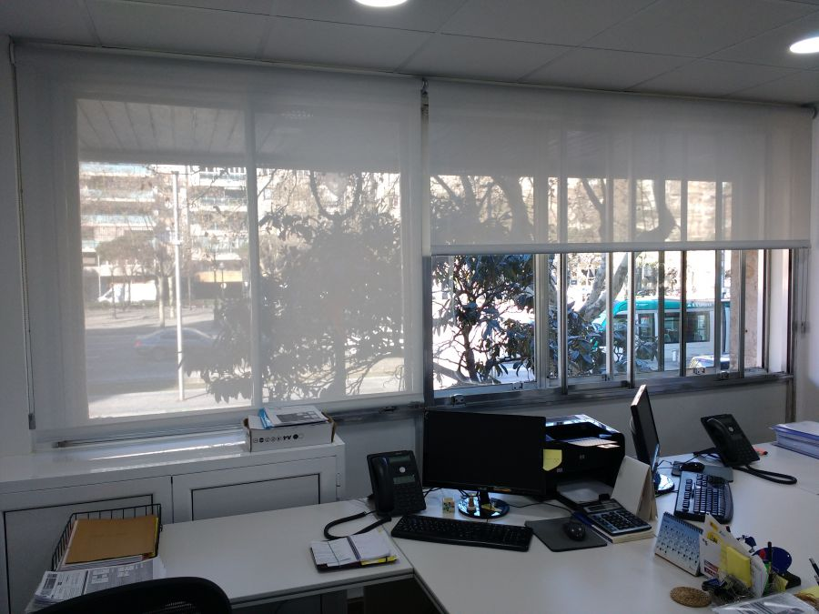 Cortinas enrollables con tejido técnico screen de color blanco instaladas en oficina
