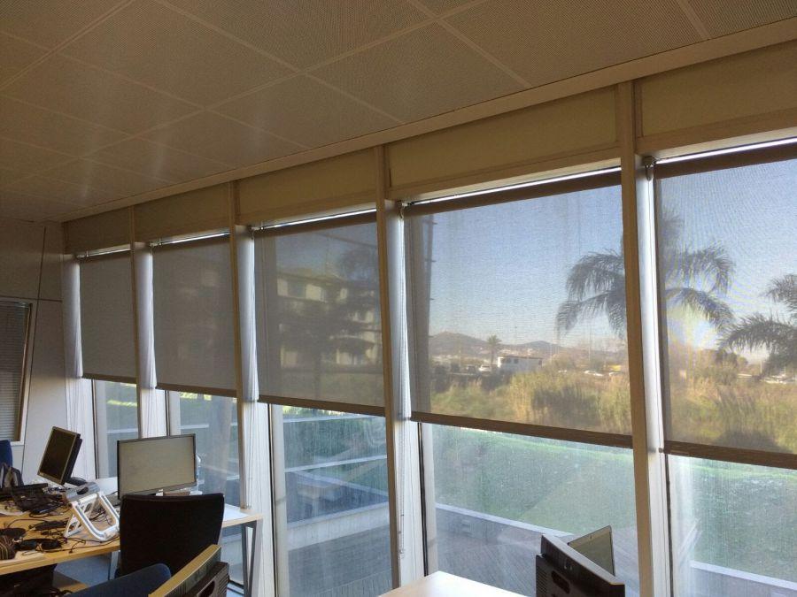 Cortinas enrollables guiadas por cable en plano inclinado instaladas en oficina