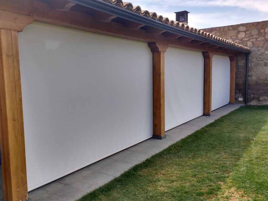 Cortinas enrollables de exterior color blanco para porche en casa con jardín