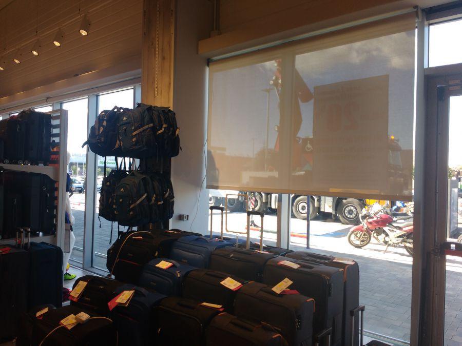 Cortinas enrollables motorizadas con tejido técnico screen instaladas en tienda de centro comercial en Terrassa
