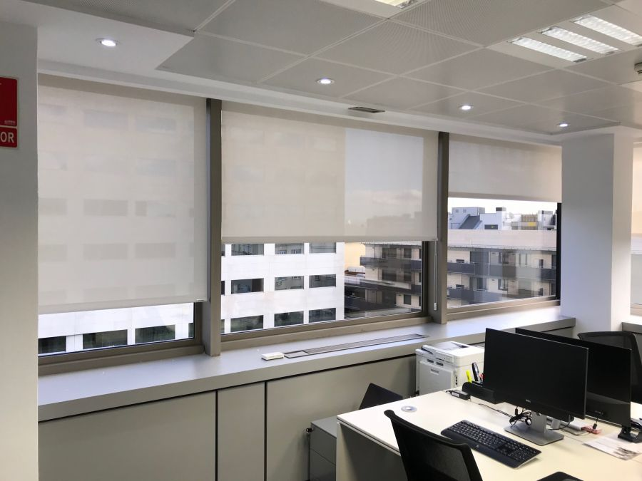Vista lateral cortinas enrollables tejido técnico screen color blanco instaladas en oficina